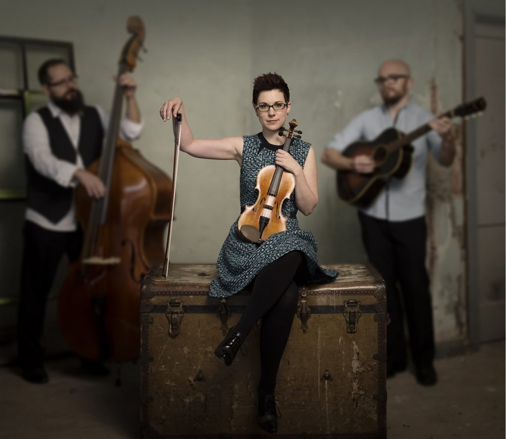 April Verch, sitting with a fiddle. Her two bandmates stand behind her, one with a stand-up bass and the other with a guitar.