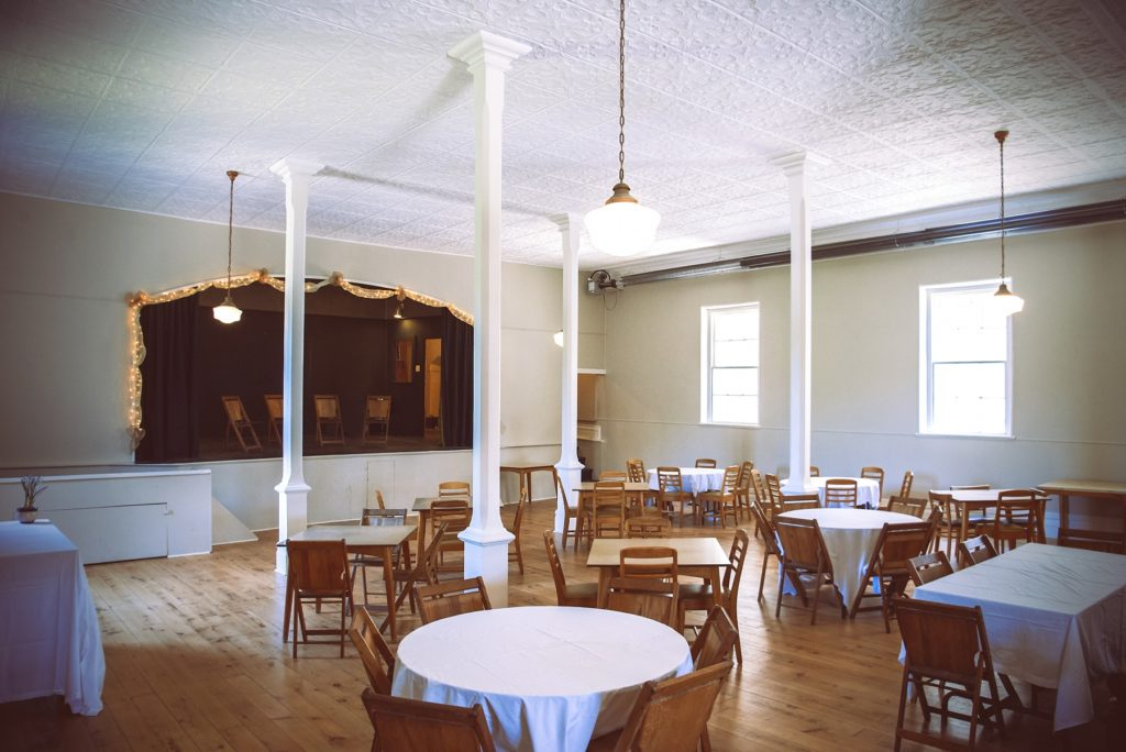 An indoor shot of Delta Old Town Hall, showing the stage and tables with wood chairs around them.