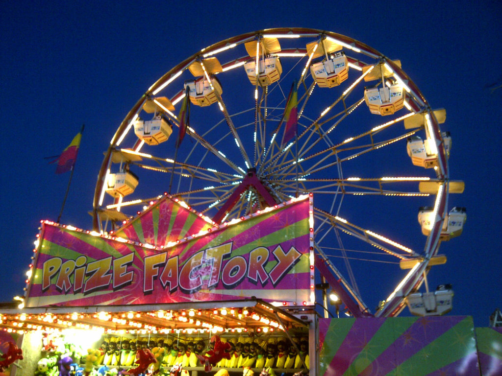 A night shot of the Ferris wheel at the Kingston Fall Fair with a carnival game in the foreground.