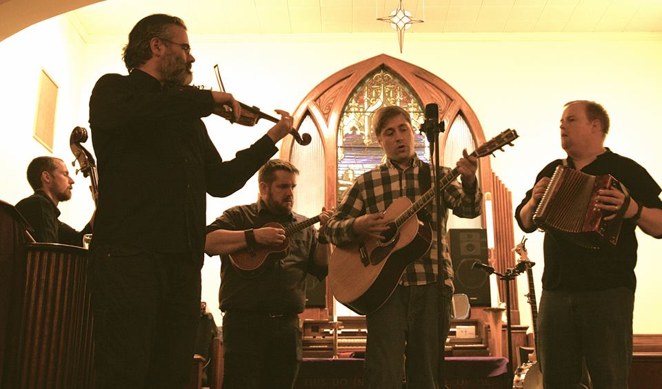 Turpin's Trail performing onstage in a church.
