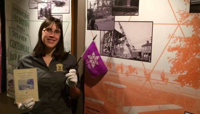 A female Brockville Museum staff member with white gloves holding a Canada centenary flag in front of an exhibit.