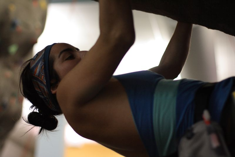 A young woman climbing the underside of an indoor climbing wall.