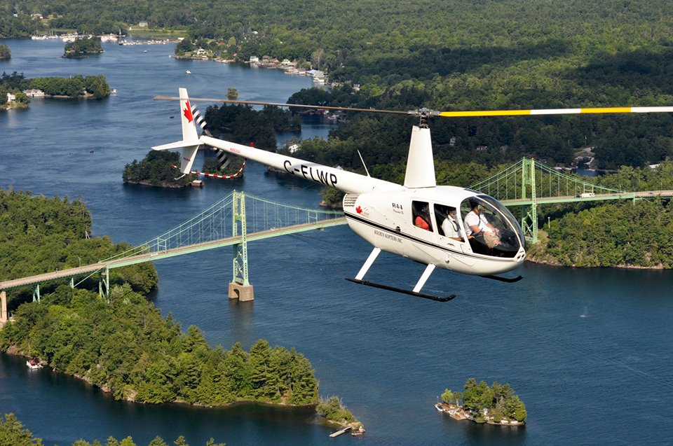 A white helicopter in the foreground and a green bridge and small islands in the background.
