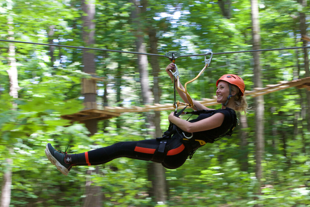 A young woman with a smile zip-lining through a forest.