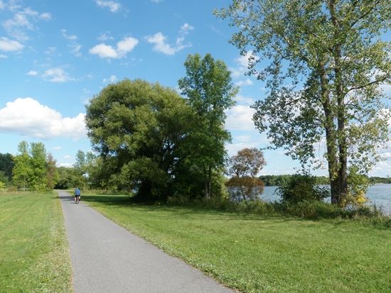 Cyclist on the Waterfront Trail recreational path at Ingleside, Ontario along the St. Lawrence River