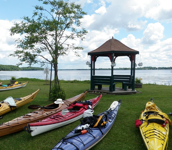 Sea kayaks parked on grassy shore in Westport Harbour, views of Upper Rideau Lake and gazebo