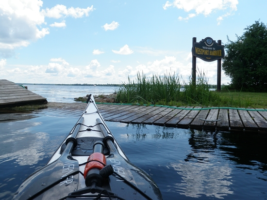 Sea kayak approaching low dock at Westport Harbour with views of Upper Rideau Lake