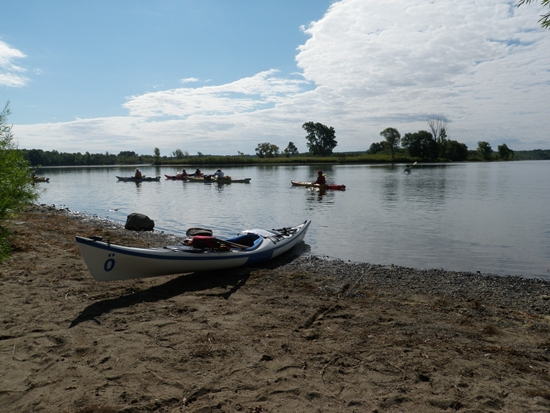 Sea kayaks launching from sandy shore at Ingleside, Ontario, on the St. Lawrence River