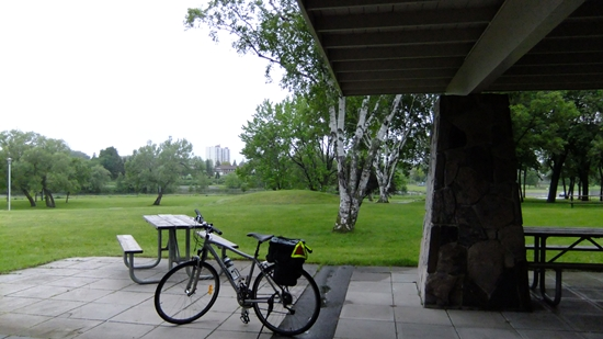 Bicycle parked under pavilion with picnic tables on a hill in Zwick's Park