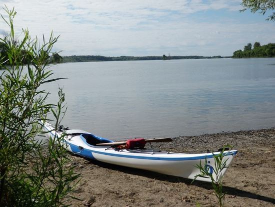 Sea kayak on sandy shore on the St. Lawrence River at Ingleside, Ontario overlooking islands